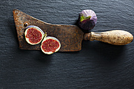 Sliced and whole fig and rusty cleaver on slate - CSF28302