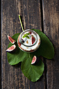 Glass of Mascarpone cream with fig compote and walnuts on fig leaf and dark wood - CSF28308