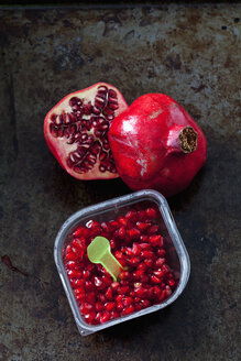 Pomegranate seed and plastic spoon in plastic box and two halves of pomegranate - CSF28338