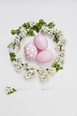 Hand dyed pink Easter eggs in cherry blossom nest on wooden background - GWF05263