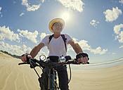 France, Bretagne, Sainte-Anne la Palud, Plage de Treguer, senior man riding mountain e-bike on beach - LAF01914
