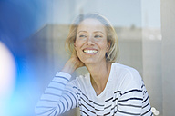 Portrait of laughing blond woman behind window pane - PNEF00017