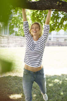 Portrait of laughing blond woman swinging at branch of a tree - PNEF00020