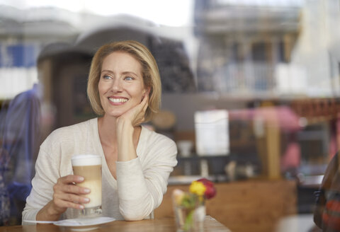 Portrait of smiling woman drinking Latte Macchiato in a coffee shop - PNEF00023