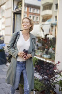 Portrait of smiling woman walking on pavement in front of a flower shop - PNEF00029