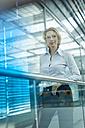 Portrait of businesswoman behind glasspane - PNEF00032