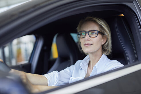 Blond businesswoman wearing glasses driving car - PNEF00038