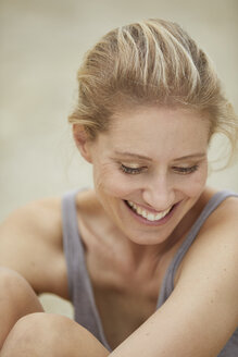 Portrait of laughing blond woman sitting on the beach - PNEF00047