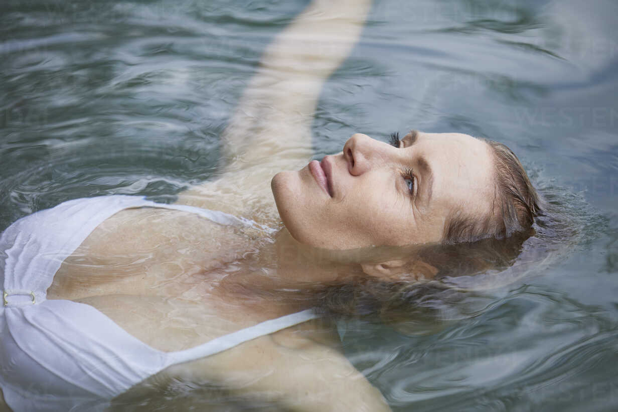 Portrait of relaxed woman floating on water - PNEF00050 - Philipp Nemenz/Westend61