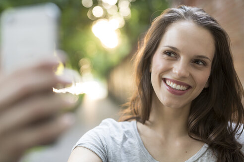 Portrait of happy young woman outdoors taking a selfie - PNEF00058