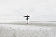 Netherlands, Ouddorp, back view of woman with arms outstretched standing on the beach in autumn - CHPF00435