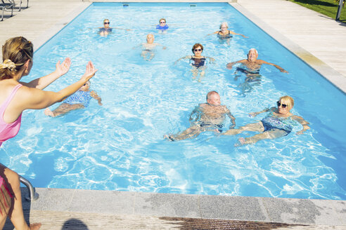 Group of seniors with trainer doing water gymnastics in pool - PNPF00099