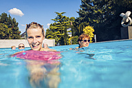 Portrait of happy woman with group of seniors swimimng in swimming pool - PNPF00111