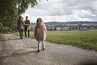 Back view of little girl watching her parents holding hands - KMKF00003