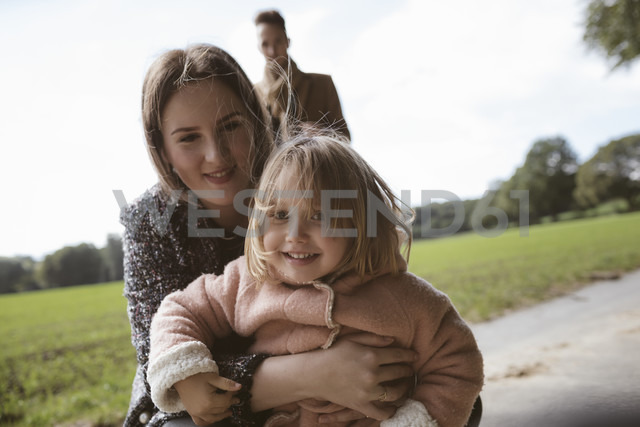 Portrait of happy blond little girl in her mothers arms - KMKF00006