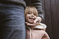 Portrait of blond little girl standing beside her father - KMKF00012