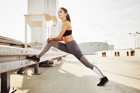 Young woman stretching during city workout - BSZF00045