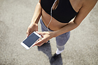 Close-up of woman holding smartphone during workout - BSZF00054