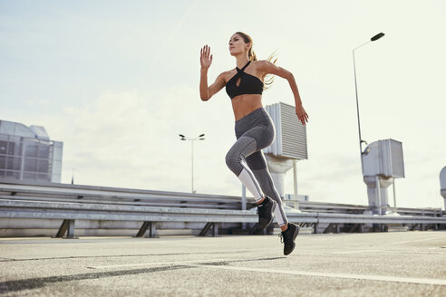 Young woman doing running exercises in the city - BSZF00057