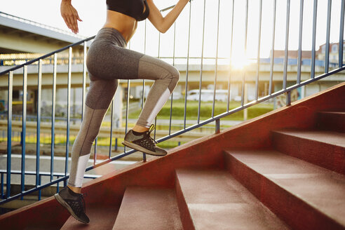 Woman running on stairs in the city - BSZF00060