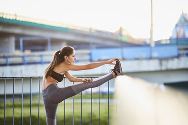 Young woman stretching during city workout - BSZF00063