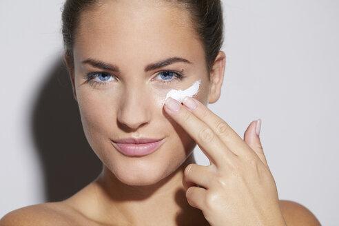 Portrait of beautiful young woman applying skin cream - PNEF00074