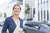 Smiling businesswoman holding tablet in the city - PNEF00095