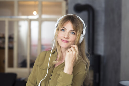 Smiling blond woman listening to music with headphones - PNEF00104