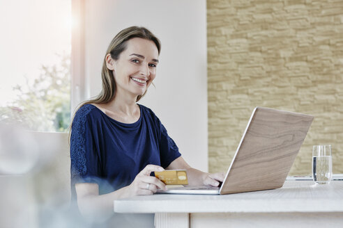 Portrait of smiling woman at home shopping online - RORF01015