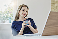 Woman at home with coffee mug and laptop - RORF01021