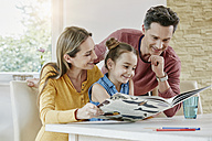 Happy family at home looking at picture book - RORF01024