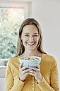 Portrait of happy woman holding bowl with muesli - RORF01027