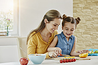 Happy mother with daughter at home cutting vegetables - RORF01030