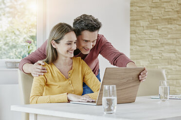 Happy couple at home using laptop - RORF01036