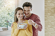 Happy couple sharing muesli at home - RORF01039