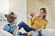 Happy mother and daughter playing with cuddly toy at home - RORF01042