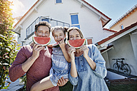 Portrait of happy family with slices of watermelon in front of their home - RORF01045