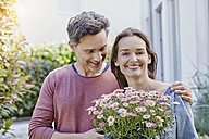 Portrait of smiling couple with flowers in front of their home - RORF01048