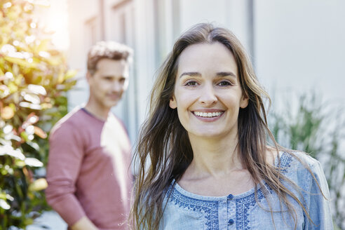 Portrait of smiling woman with man in background - RORF01051
