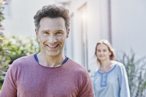 Portrait of smiling man with woman in background - RORF01054