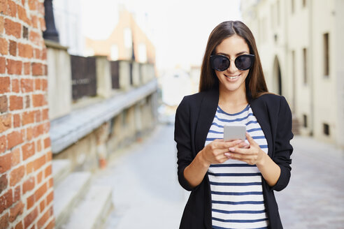 Young woman wearing sunglasses using phone outdoors - BSZF00064