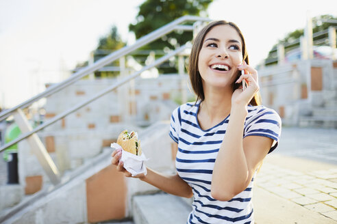 Young woman talking on phone and eating bagel in the city - BSZF00067