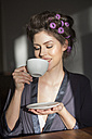 Young woman with curlers drinking cup of coffee - PNEF00117