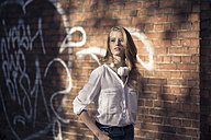 Portrait of young woman with headphones in front of brick wall - PNEF00121