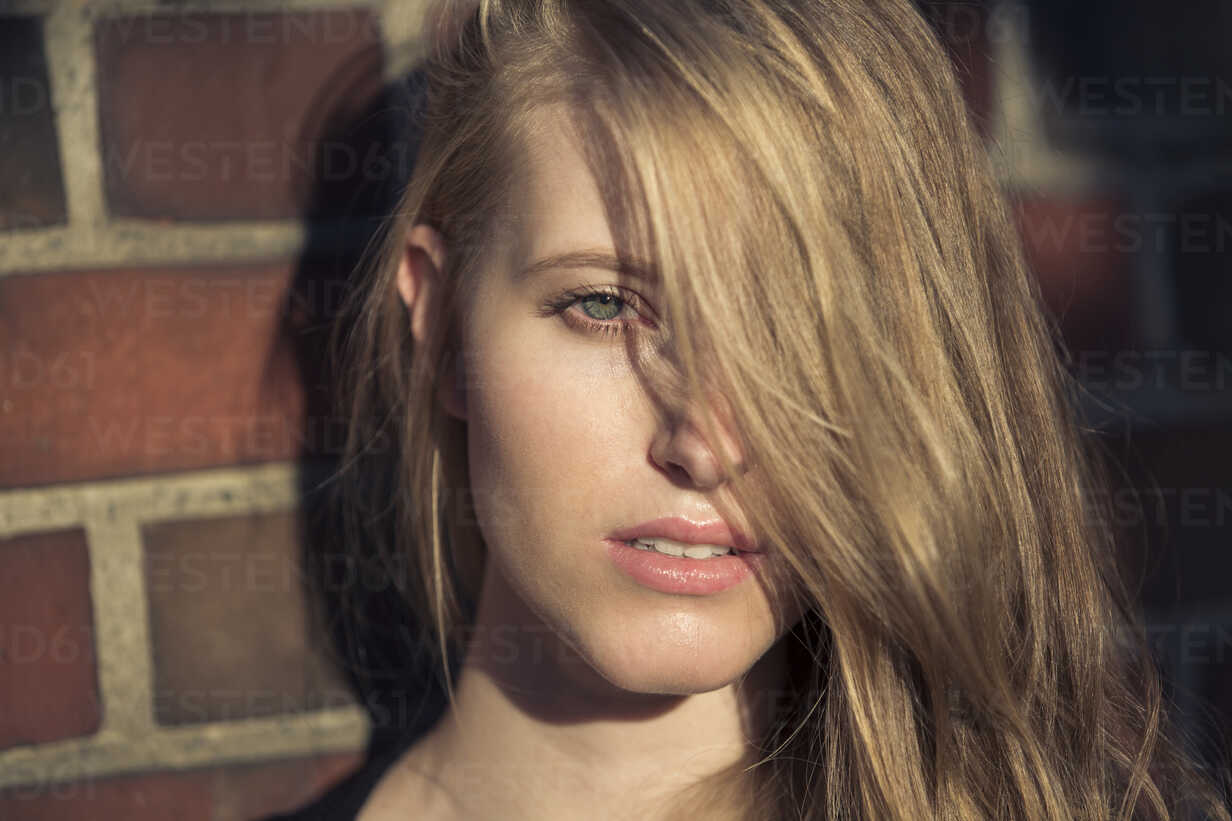 Portrait of blond young woman in front of brick wall - PNEF00127 - Philipp Nemenz/Westend61