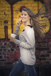 Portrait of laughing woman with coffee to go on the phone - PNEF00130