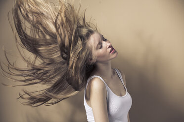 Portrait of blond young woman tossing her hair - PNEF00133