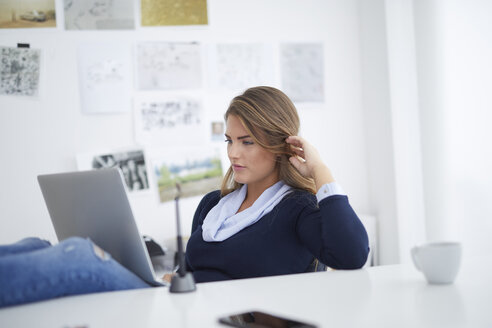 Young woman using laptop at desk in office - PNEF00138