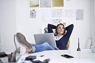 Young woman with laptop at desk in office leaning back - PNEF00141