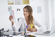 Young woman looking at notes at desk in office - PNEF00144